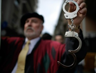 ATHENS , GREECE - FEBRUARY 24:  A demonstrator holds up a pair of handcuffs while participating in a 24-hour general strike on February 24, 2010 in Athens, Greece. Greece ground to a halt and flights were grounded as unions staged a one-day general strike in protest against the Government's austerity measures designed to contain the massive public deficit.  (Photo by Milos Bicanski/Getty images)